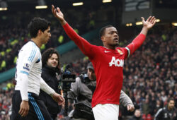 Manchester United's Patrice Evra, right, celebrates alongside Liverpool's Luis Suarez after Manchester United's 2-1 win over their Merseyside rivals following their English Premier League soccer match at Old Trafford Stadium, Manchester, England, Saturday, Feb. 11, 2012. (AP Photo/Jon Super)