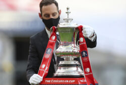 The trophy is handled by a man wearing a face mask after the FA Cup final soccer match between Arsenal and Chelsea at Wembley stadium in London, England, Saturday, Aug.1, 2020. (Catherine Ivill/Pool via AP)  XVG219