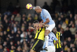 Manchester City's Vincent Kompany, top, jumps for the ball with Watford's Troy Deeney during the English Premier League soccer match between Watford and Manchester City at Vicarage Road stadium in Watford, England, Tuesday, Dec. 4, 2018. (AP Photo/Frank Augstein)