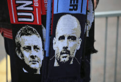 A man sells scarves with pictures of Manchester United manager Ole Gunnar Solskjaer, left, and Manchester City coach Pep Guardiola outside the stadium before before the English Premier League soccer match between Manchester United and Manchester City at Old Trafford Stadium in Manchester, England, Wednesday April 24, 2019. (AP Photo/Jon Super)