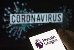 In this photo illustration the top level of the English football league Premier League logo seen displayed on a smartphone with a computer model of the COVID-19 coronavirus on the background. (Photo by Budrul Chukrut / SOPA Images/Sipa USA)