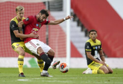 Manchester United's Bruno Fernandes kicks the ball as Southampton's James Ward-Prowse, left, watches during the English Premier League soccer match between Manchester United and Southampton at Old Trafford in Manchester, England, Monday, July 13, 2020. (AP Photo/Dave Thompson,Pool)  XMB150